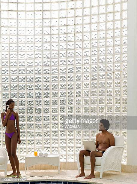 Young couple in swimwear at poolside, using laptop and mobile phone