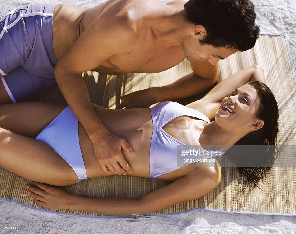 Young Couple in Swimwear Lie on a Mat on the Beach, Embracing and Laughing : Stock Photo