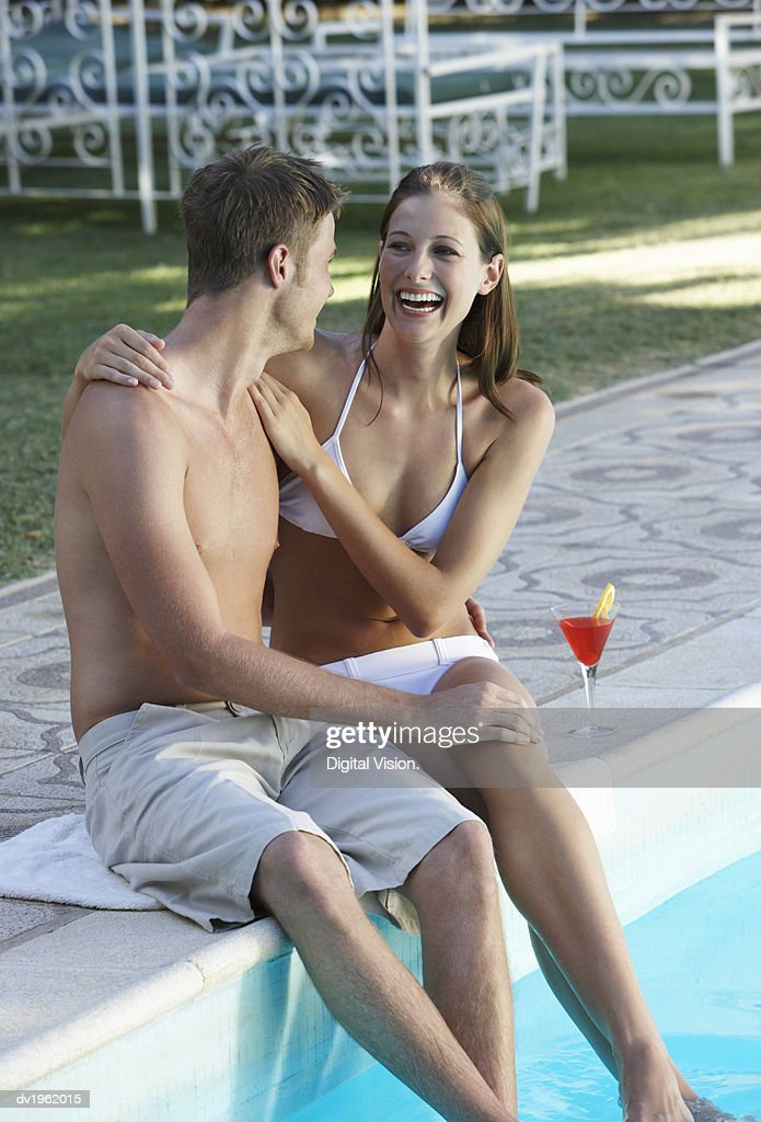 Young Couple in Swimwear Sit by a Swimming Pool, Woman Laughing With Her Arm Around the Man : Stock Photo