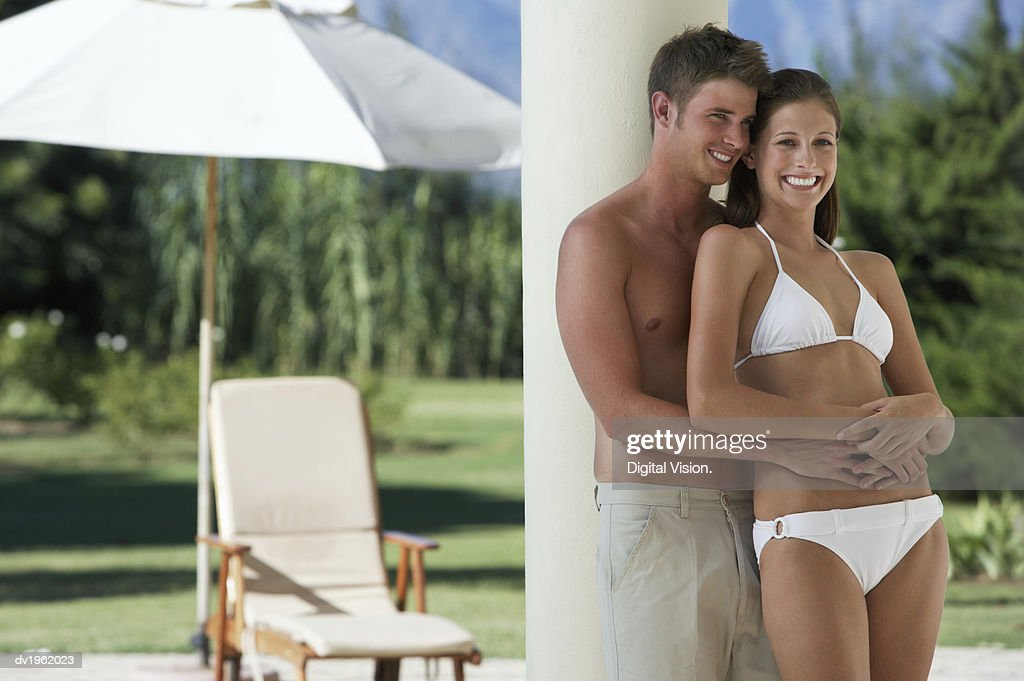 Young Couple in Swimwear Stand on a Porch, Embracing : Stock Photo
