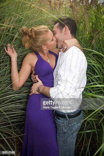 young couple in tall green grass - kissing on the mouth stock photos and pictures