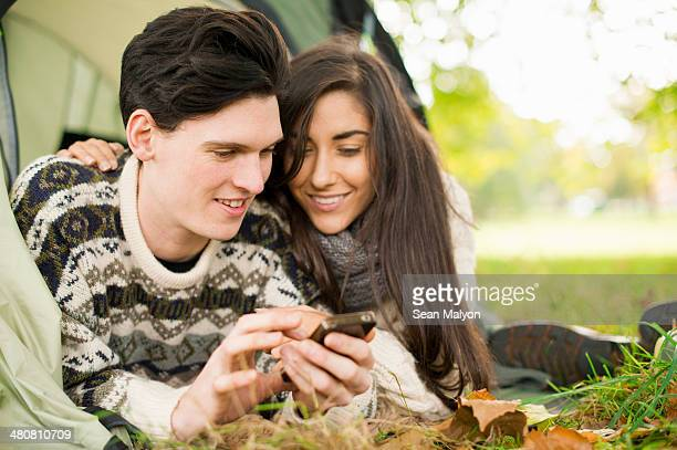 young couple in tent using smartphone - sean malyon stock pictures, royalty-free photos & images