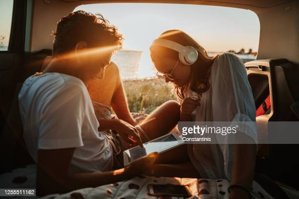 young couple in the car trunk on vacation.sea and sunset in background - greece stock pictures, royalty-free photos & images