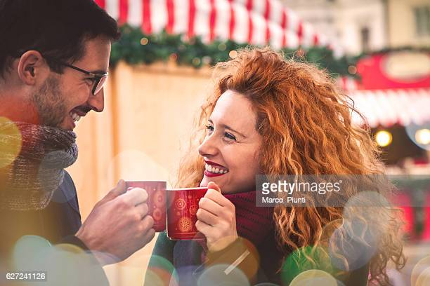 Young couple in the city during christmas drink hot coffee