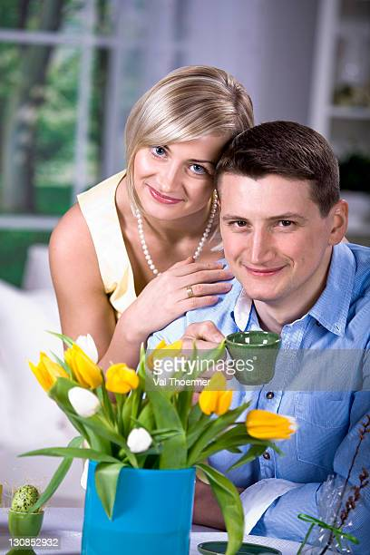 young couple in the living room, tulips, easter egg - happy resurrection day stock pictures, royalty-free photos & images