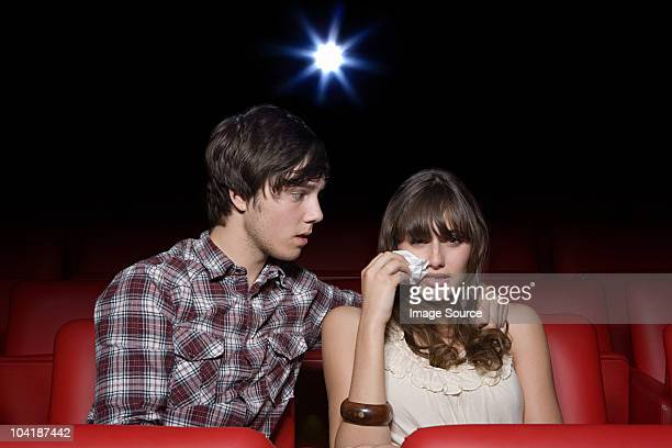Young couple in the movie theater, both crying