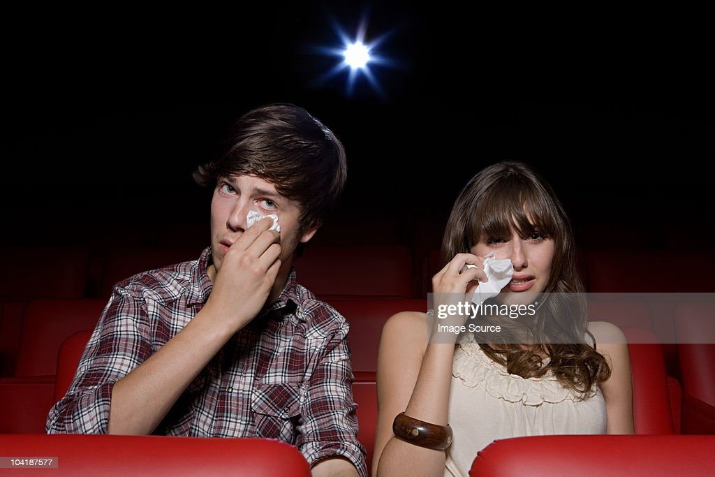 Young couple in the movie theater, woman crying : Stock Photo