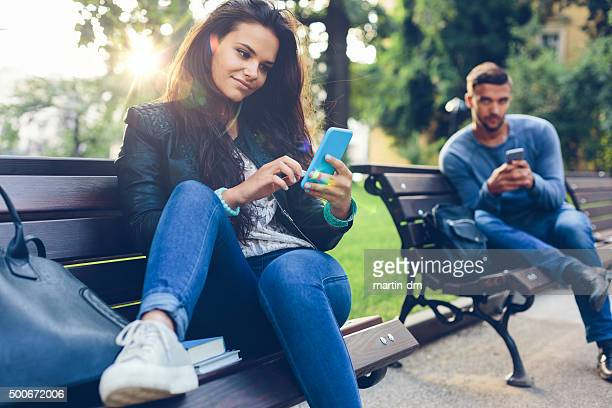 young couple in the park texting on smartphones - flirting stock pictures, royalty-free photos & images