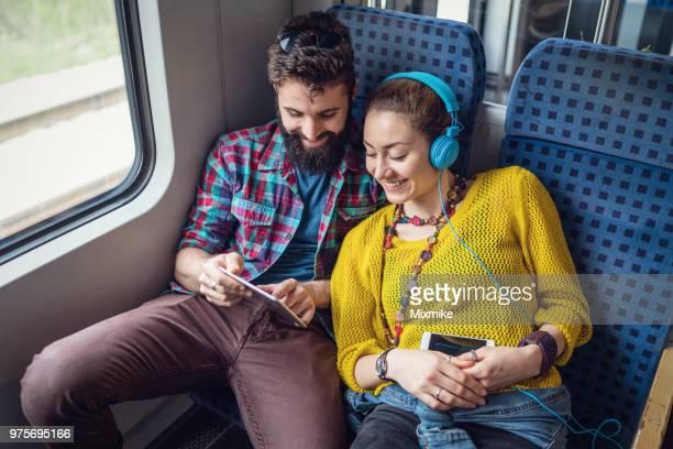 jong koppel in de trein die surfen op het net op de tablet pc - trein stockfoto's en -beelden