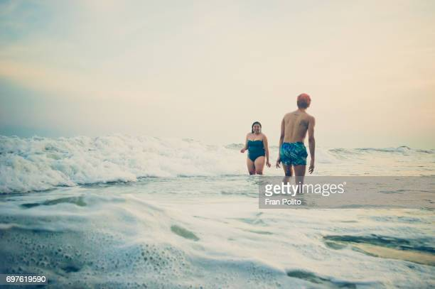 A young couple in the water at the beach.