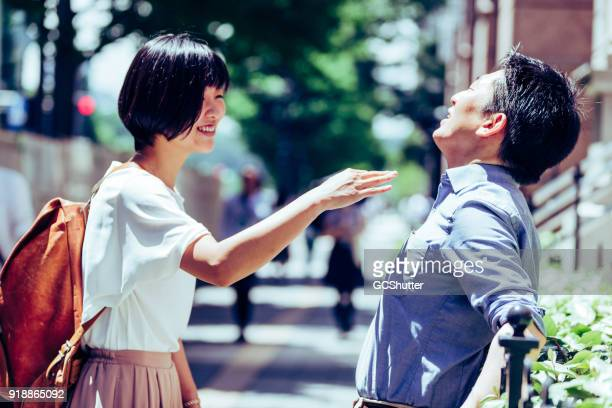 Young couple in Tokyo teasing each other on the street