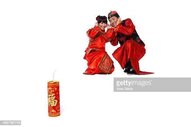 young couple in traditional clothes with fire cracker - 一張羅 ストックフォトと画像