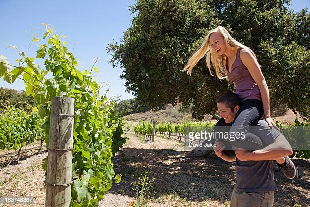 Young couple in vineyard, man giving woman piggy back