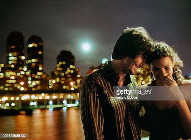 Young couple in waterfront park at night smiling