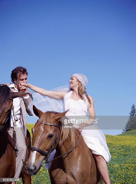 Young Couple in Wedding Dress Riding Horses