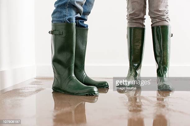 young couple in wellington boots on flooded floor - flooding stock photos and pictures