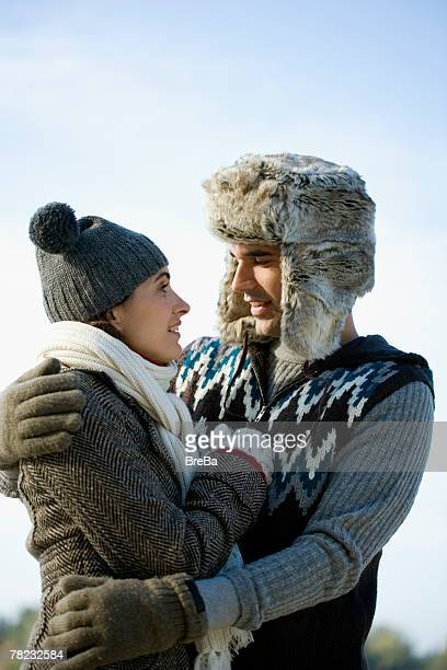 young couple in winter clothes looking at each other