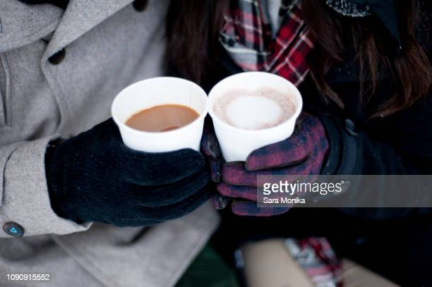 young couple in winter gloves holding takeaway drinks, close up of hands - hot chocolate stock pictures, royalty-free photos & images