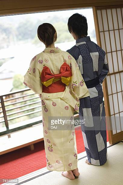 Young couple in Yukata looking outside from the window, rear view, Japan