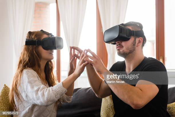 Young couple indoors enjoying virtual reality game