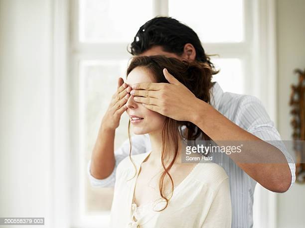 young couple indoors, man covering woman's eyes - covering stock pictures, royalty-free photos & images