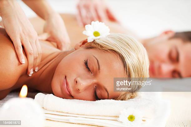 Young couple is having a back massage at spa centre.