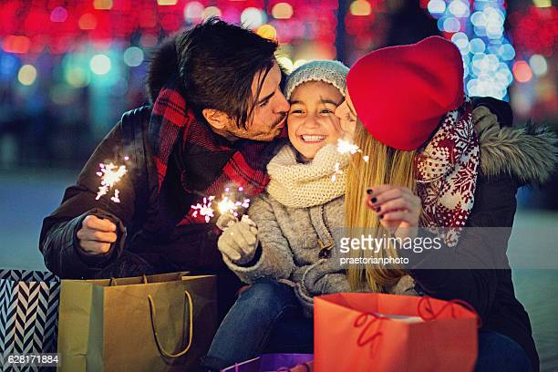 Young couple is hugging and kissing their daughter at Xmas
