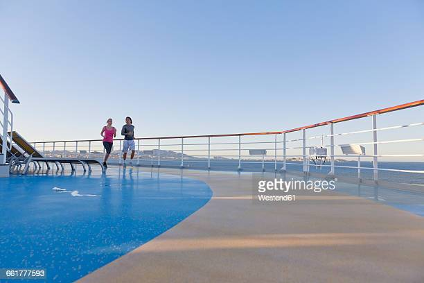 young couple is jogging around the shipdeck of a cruise ship, mediterranean sea - 乗り物に乗って ストックフォトと画像