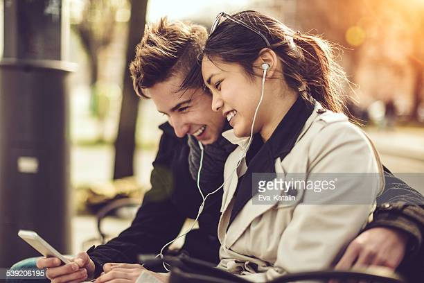 Young couple is listening music on their mobile