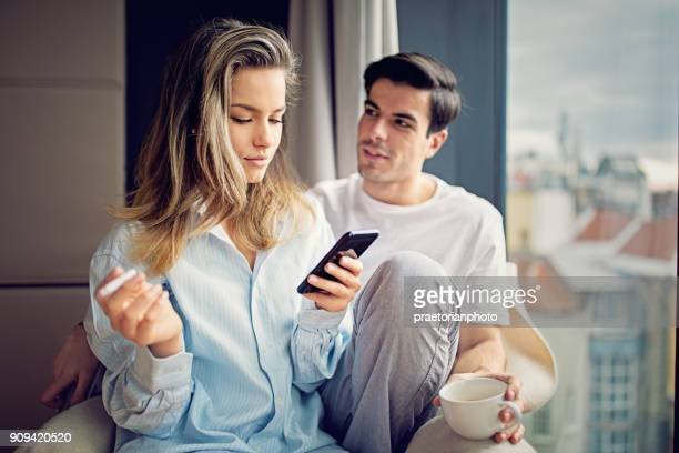 young couple is looking the city view and texting - beautiful women smoking cigarettes stock pictures, royalty-free photos & images