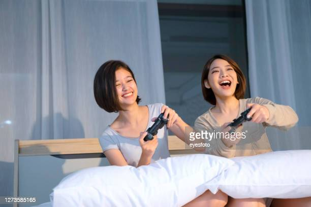young couple is playing video game in the bedroom. - new generation stock pictures, royalty-free photos & images