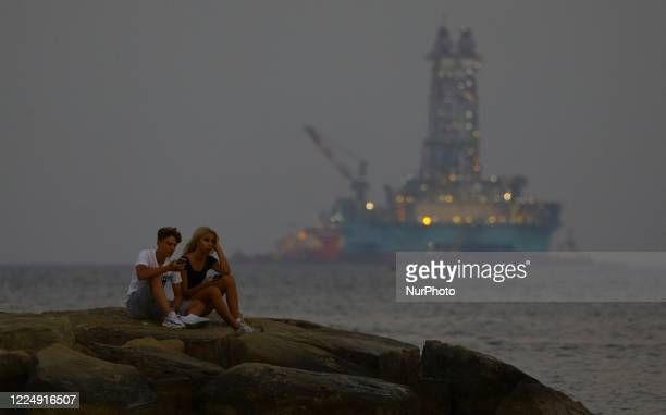 Young couple is resting on a pier amid a rig in the Mediterranean port of Limassol. Cyprus, Monday, July 6, 2020 Cyprus has in recent years been a...