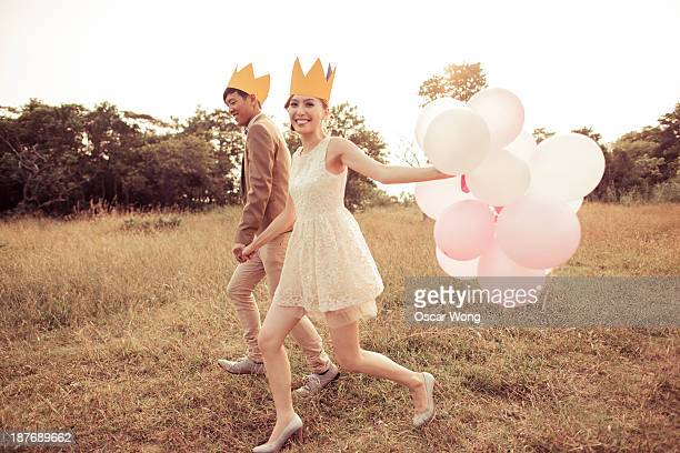 Young couple is running on the grass with balloons