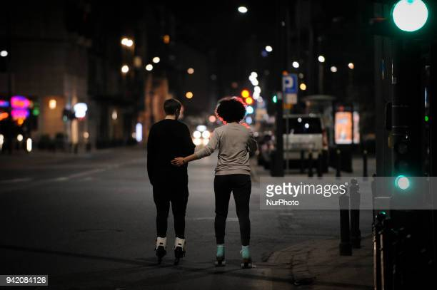 A young couple is seen rollerblading in Waraw Poland on April 4 2018 An H and M fashion fashion retail shop is seen in Warsaw Poland on April 2018