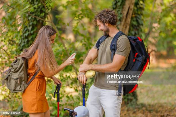 a young couple is traveling with backpacks and has problems with insects in the forest. - insect bites images stock pictures, royalty-free photos & images