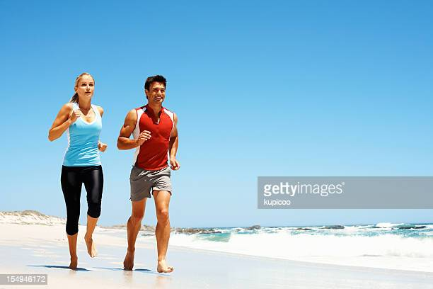 Young couple jogging by the sea