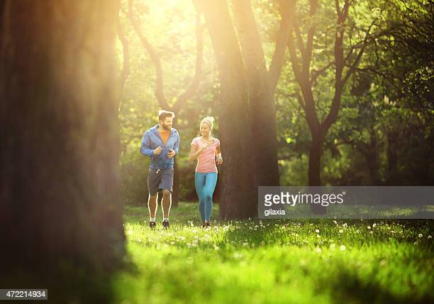 Young couple jogging in local park.