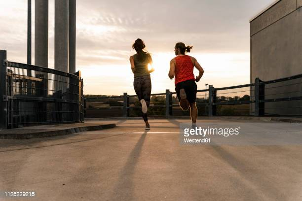young couple jogging in the morning - rennen sport stock-fotos und bilder