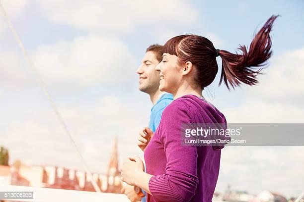 young couple jogging on bridge, osijek, croatia - ポニーテール ストックフォトと画像