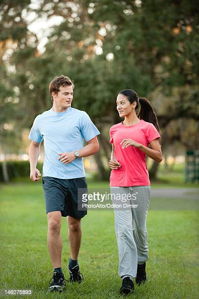 Young couple jogging on grass