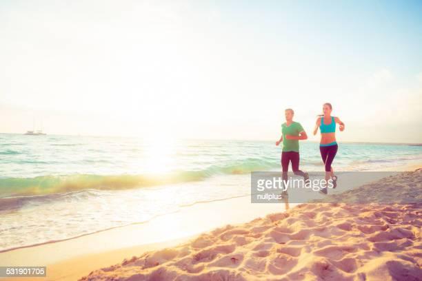 Pareja joven para correr en la playa