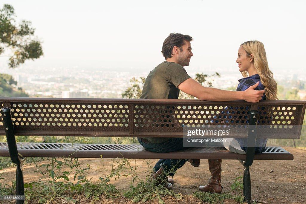 Young couple joke on park bench overlooking city : Stock Photo