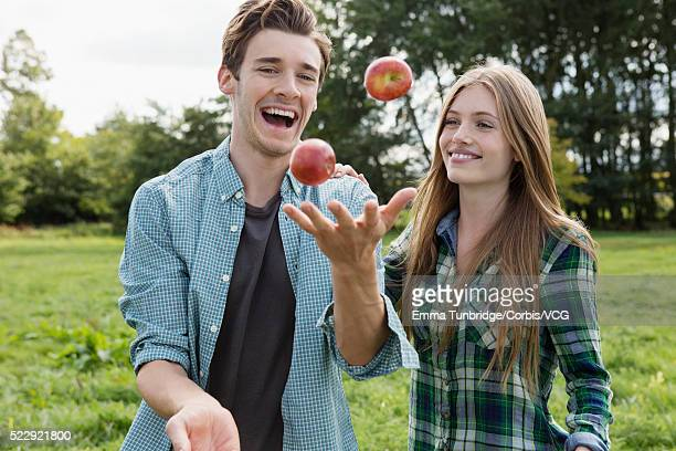 Young couple juggling apples in park, UK