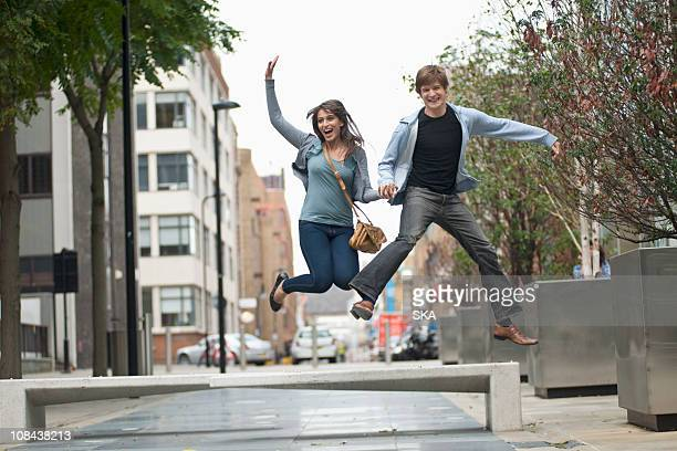 Young couple jumping in street