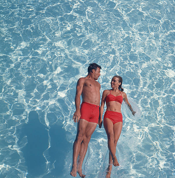 Young Couple Jumping In Swimming Pool, Smiling Wall Art