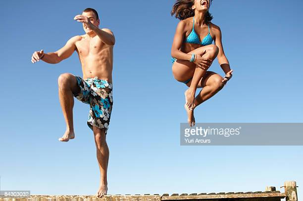 Young couple jumping of dock