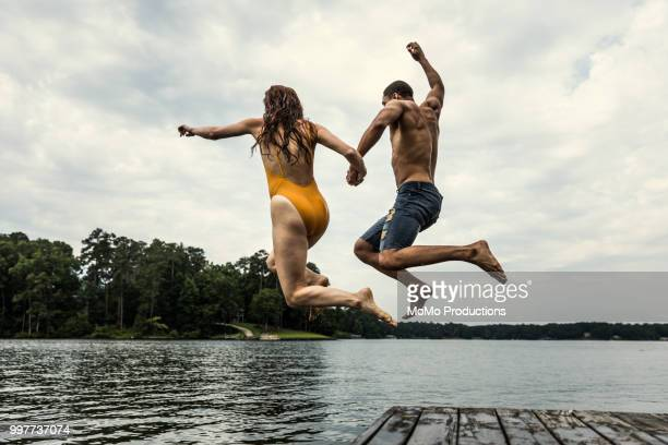 young couple jumping dock into lake