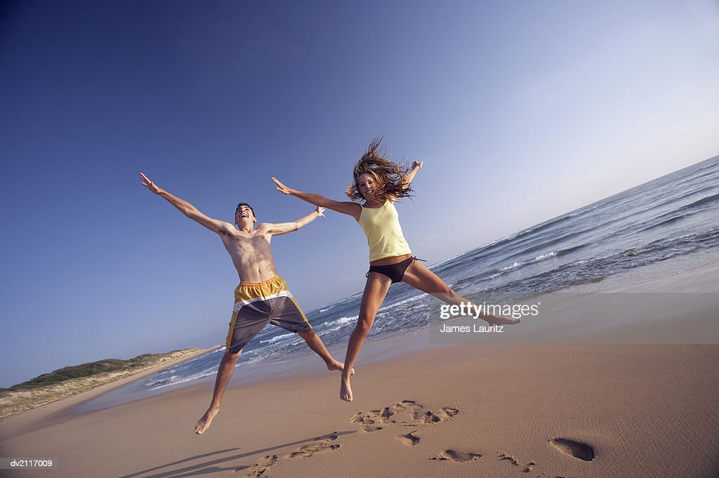 Young Couple Jumping on a Beach : Stock Photo