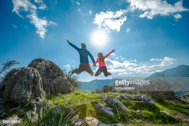 Young couple jumping on mountain