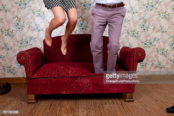Young couple jumping on old school couch